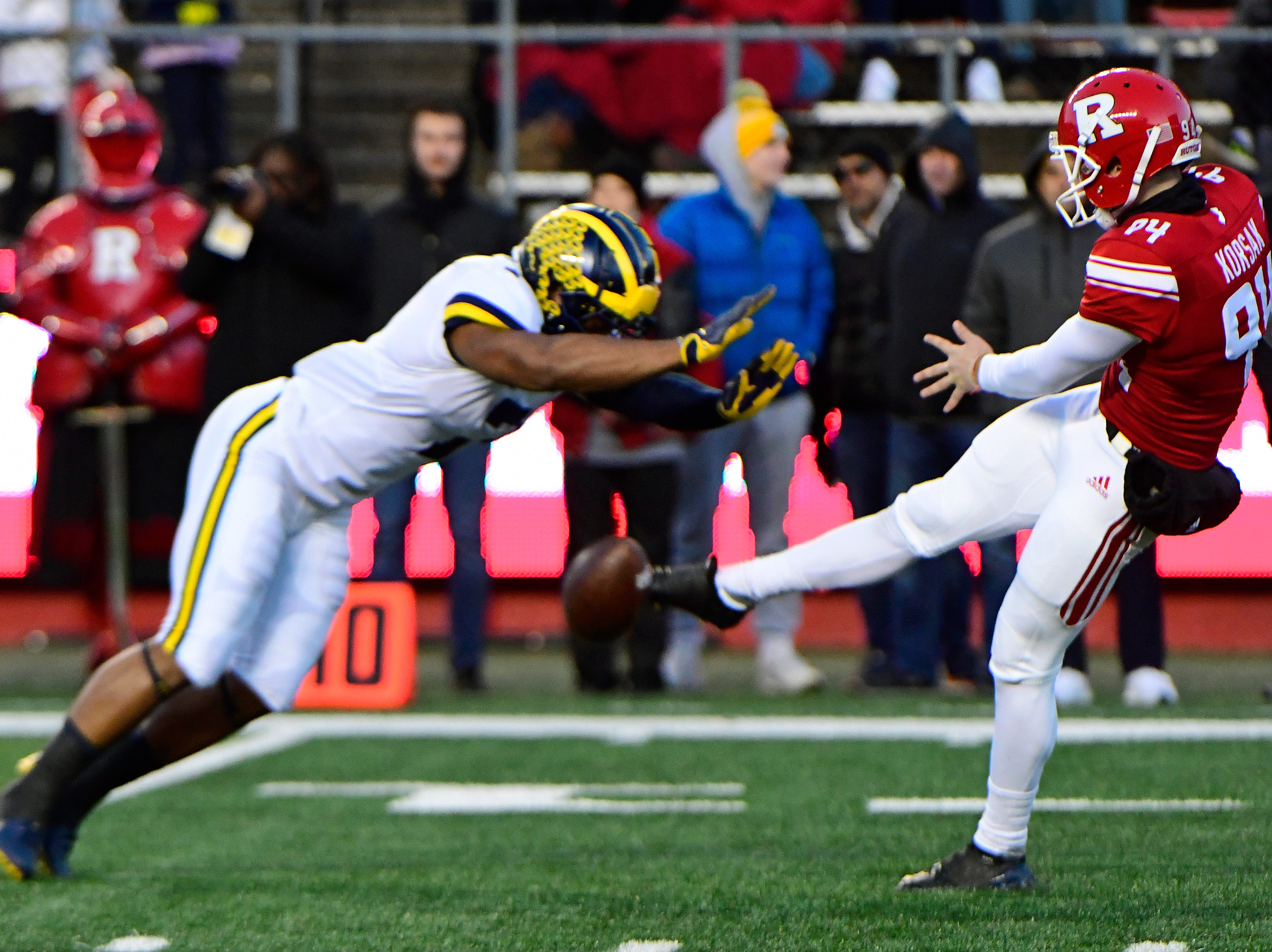 Adam Korsak of the Rutgers Scarlet Knights punts the ball in time as Khaleke Hudson of the Michigan Wolverines nearly blocks.