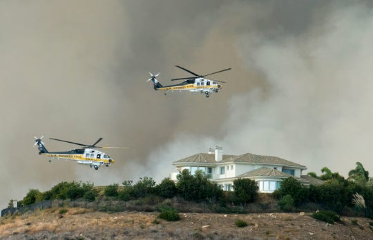 Helicopters prepare to drop water on a brush fire behind a home during the Woolsey Fire in Malibu, Calif., Friday, Nov. 9, 2018.