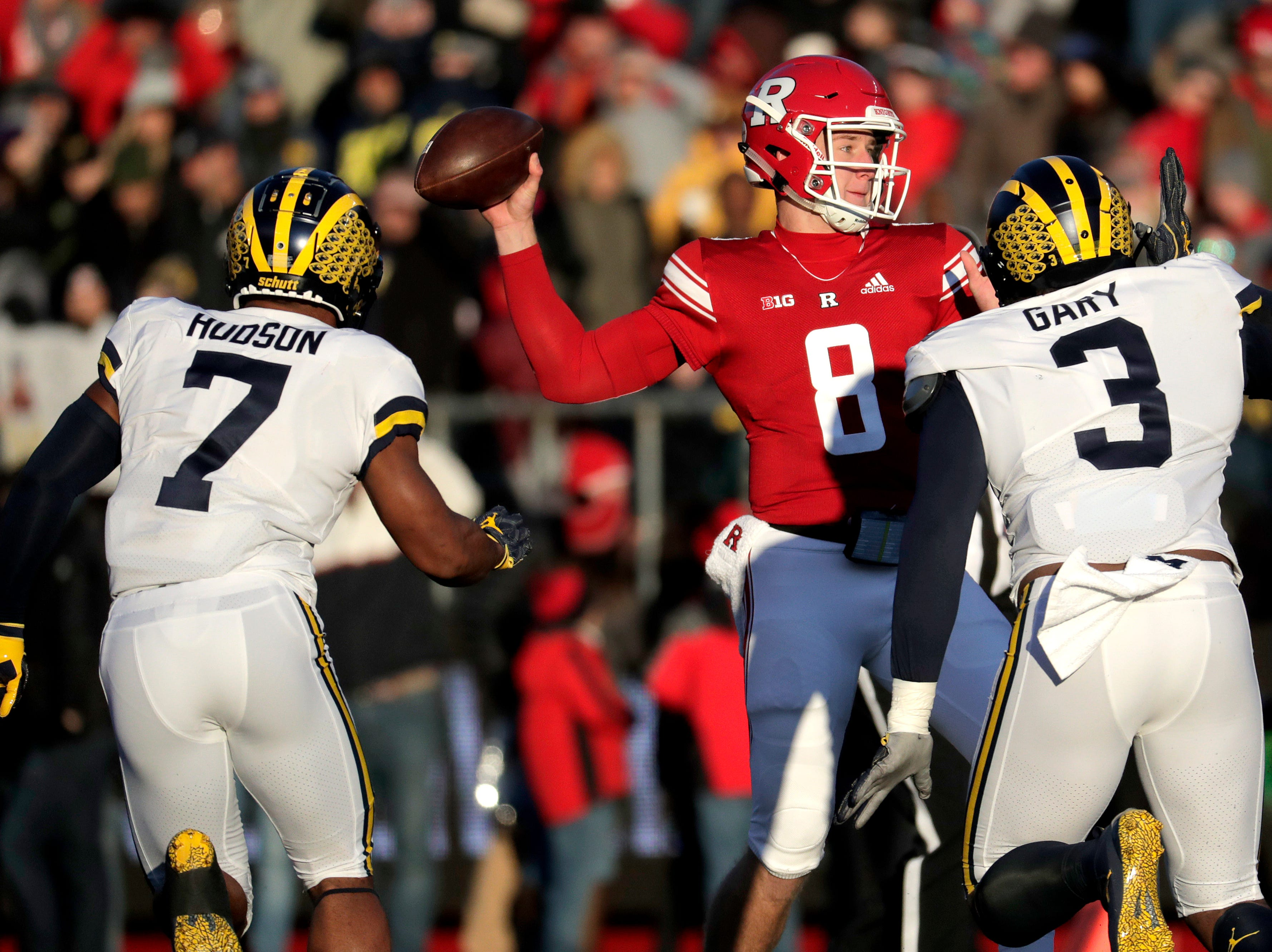 Rutgers quarterback Artur Sitkowski (8) looks to pass as Michigan linebacker Khaleke Hudson (7) and defensive lineman Rashan Gary (3) apply pressure.
