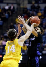 Buffalo guard Jeremy Harris (2) shoots while defended by West Virginia guard Chase Harler (14) during the first half Friday.