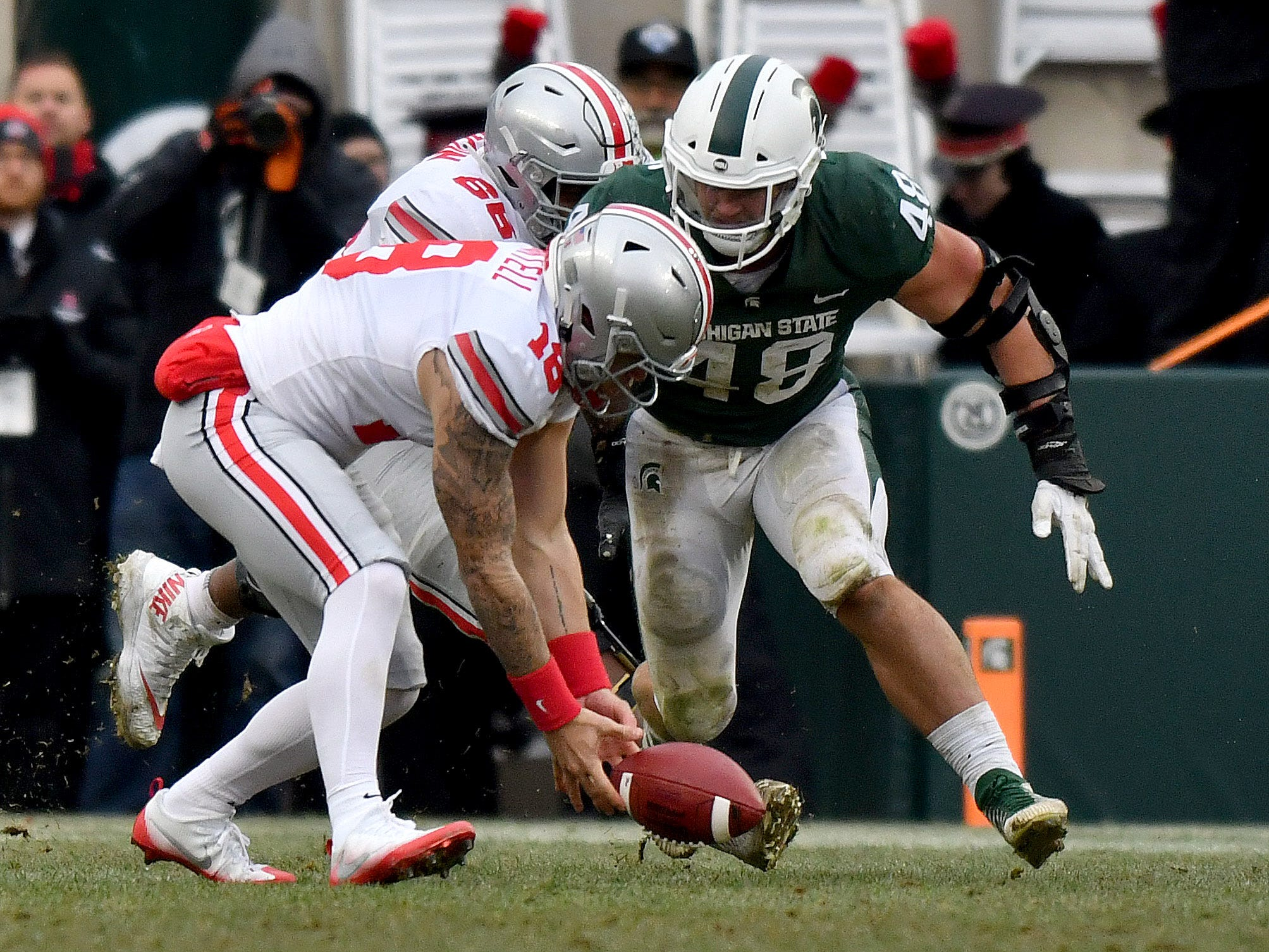 Buckeye quarterback Tate Martell fumbles the ball under pressure from Kenny Willekes in the fourth quarter and the Spartans recover it.