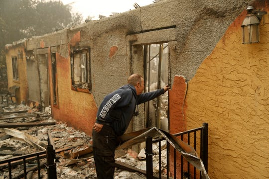 Courtenay Jenvey inspects the remains of his neighbor's home Saturday, Nov. 10, 2018, in Paradise, Calif. Jenvey was able to save his house during the fire.