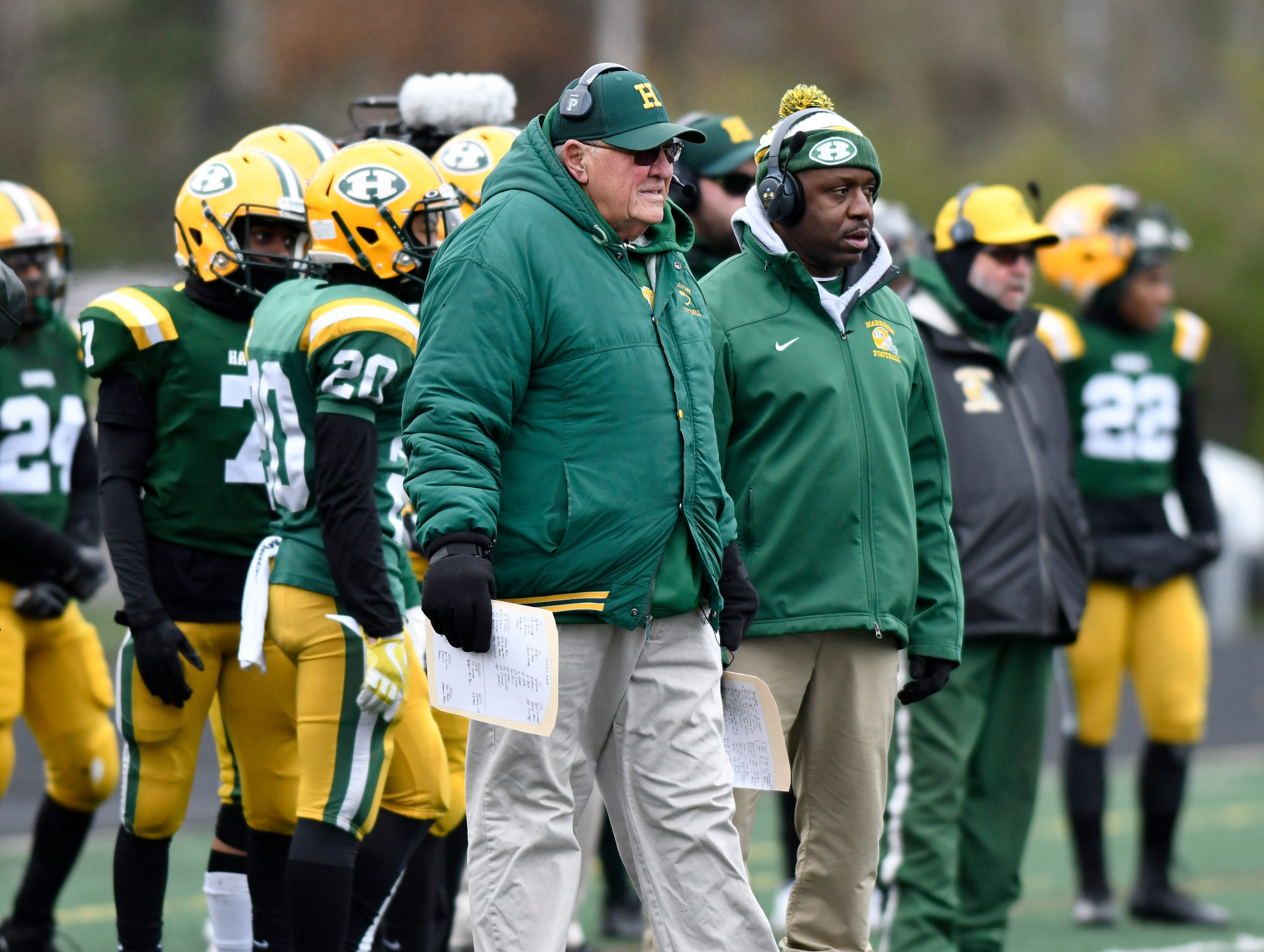 Farmington Hills Harrison football head coach John Herrington, center, watches his team play against Chelsea during the first quarter Saturday.