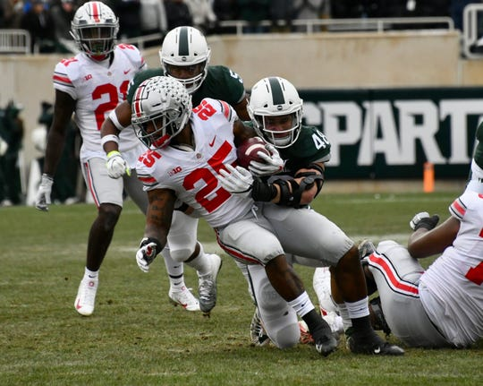 Kenny Willekes tackles Mike Weber for a loss in the first quarter.