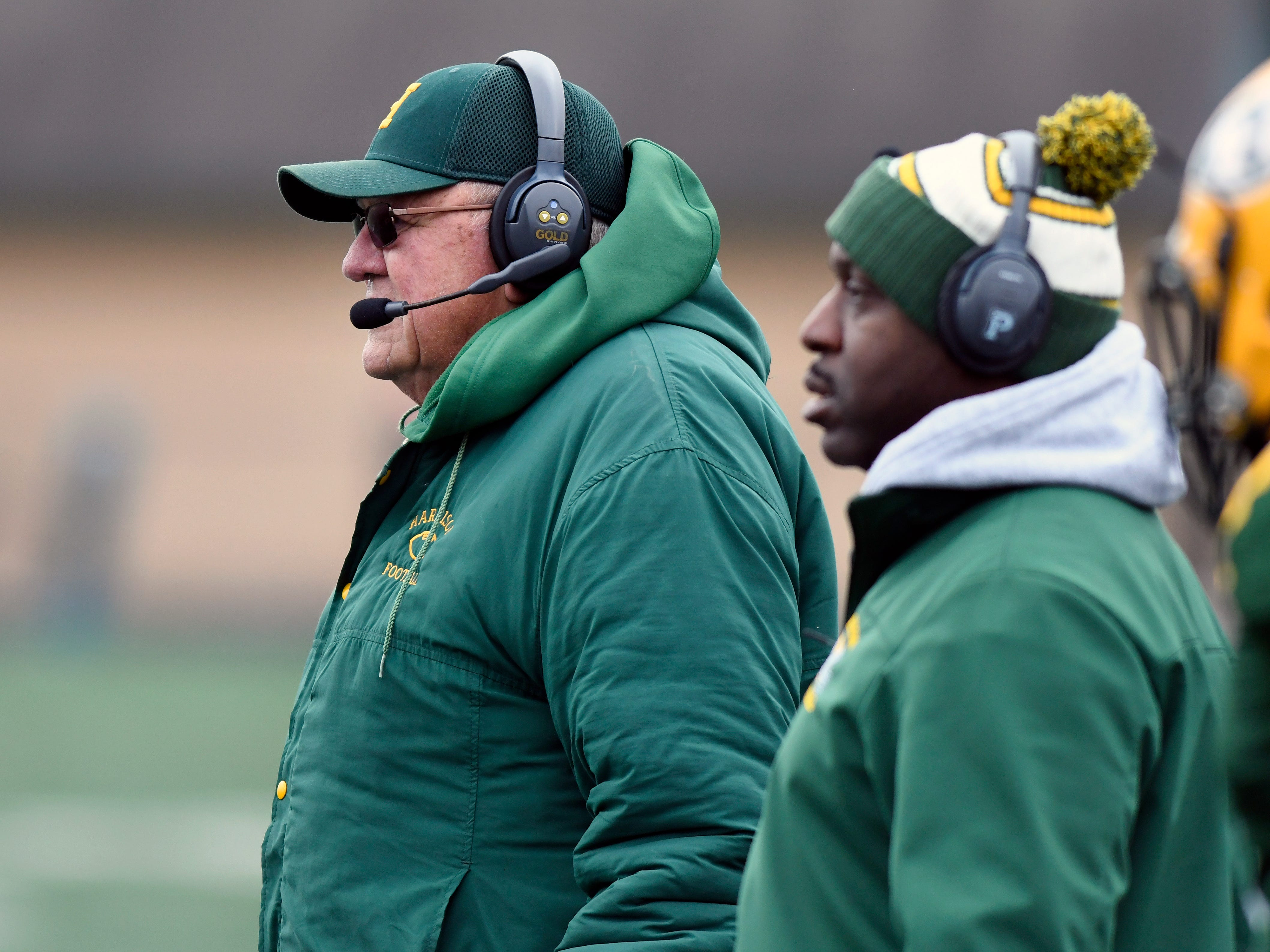 Farmington Hills Harrison football head coach John Herrington, left, watches his team play against Chelsea during the first quarter, Saturday in Farmington Hills. It would be the final game for the storied coach and his high school.