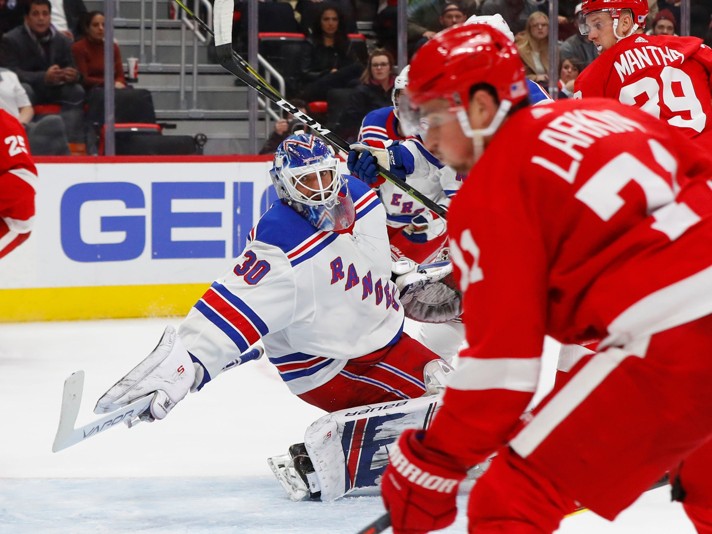 New York Rangers goalie Henrik Lundqvist (30) reaches to block a shot by Detroit Red Wings' Dylan Larkin in the second period of an NHL hockey game in Detroit, Friday, Nov. 9, 2018.