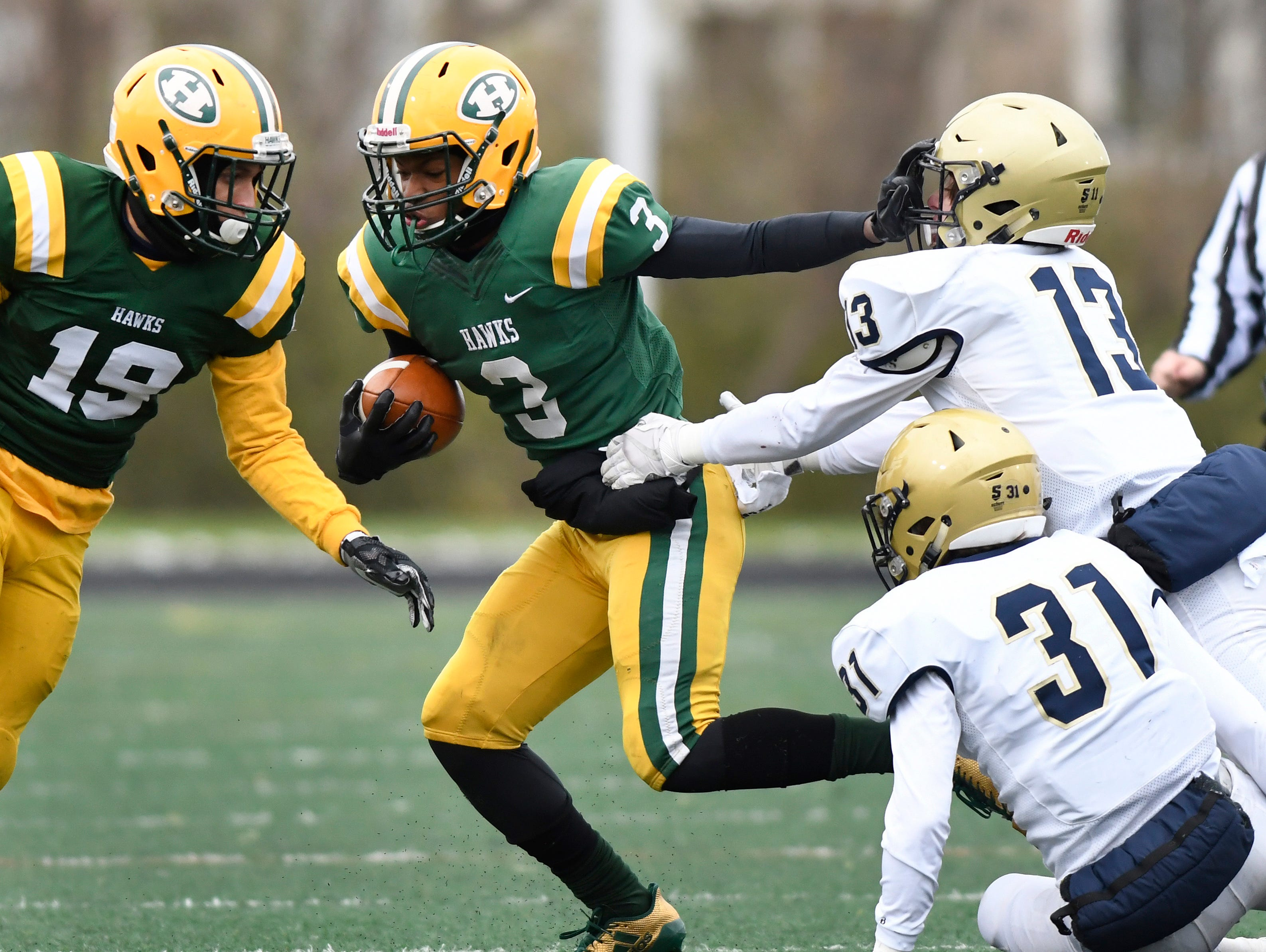 Farmington Hills Harrison running back Roderick Heard (3) runs for yardage as he pushes off during the first quarter.