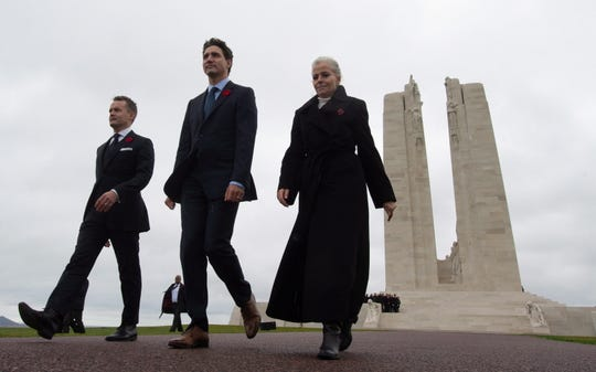 Canadian Prime Minister Justin Trudeau, center, Minister of Veterans Affairs Seamus O'Regan, left, and Canadian Ambassador to France Isabelle Hudon walk away from the memorial at Vimy Ridge, France following a ceremony Saturday, Nov.  10, 2018.