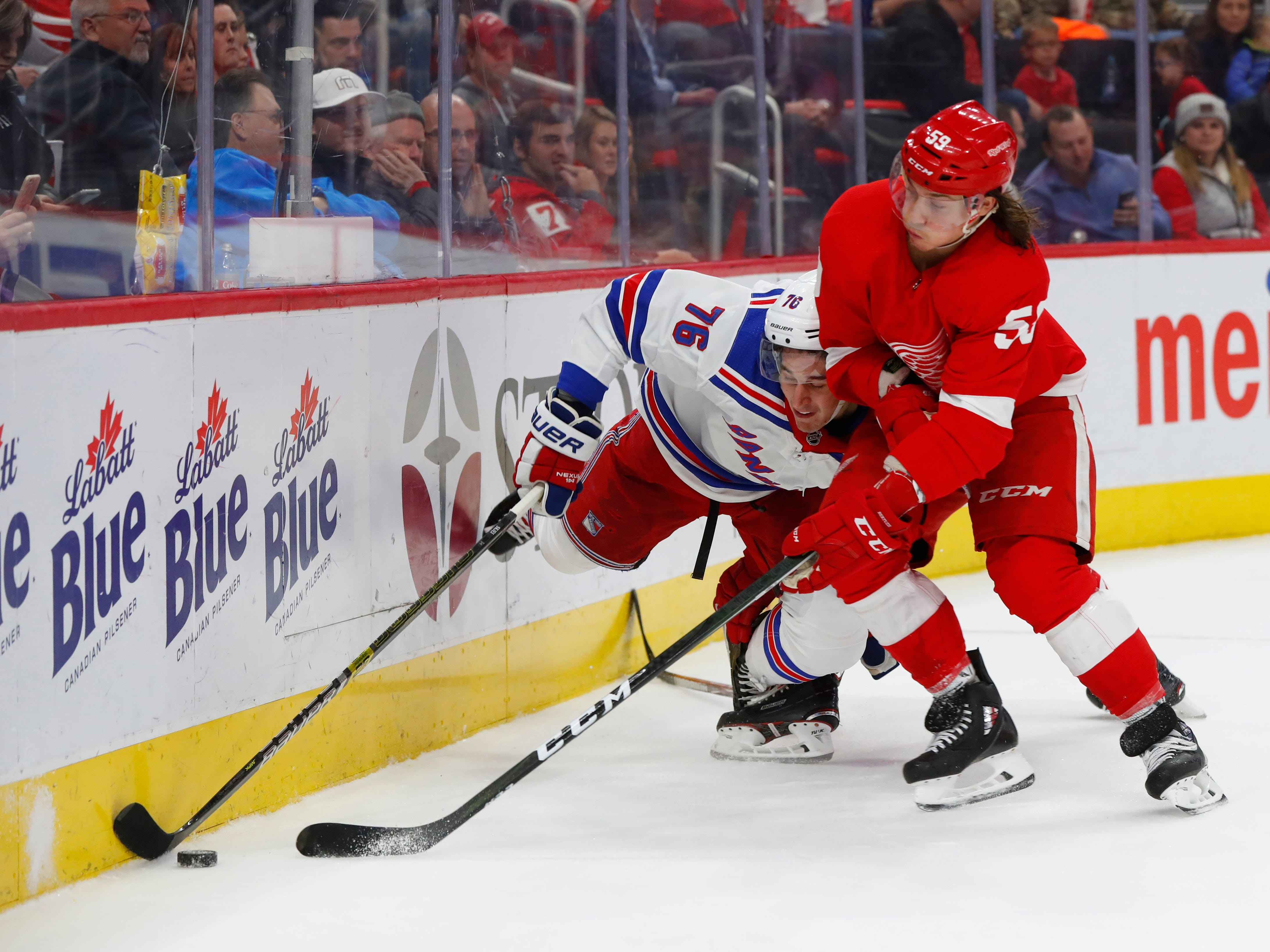Detroit Red Wings' Tyler Bertuzzi (59) and New York Rangers' Brady Skjei (76) battle for the puck in the second period of an NHL hockey game in Detroit, Friday, Nov. 9, 2018.