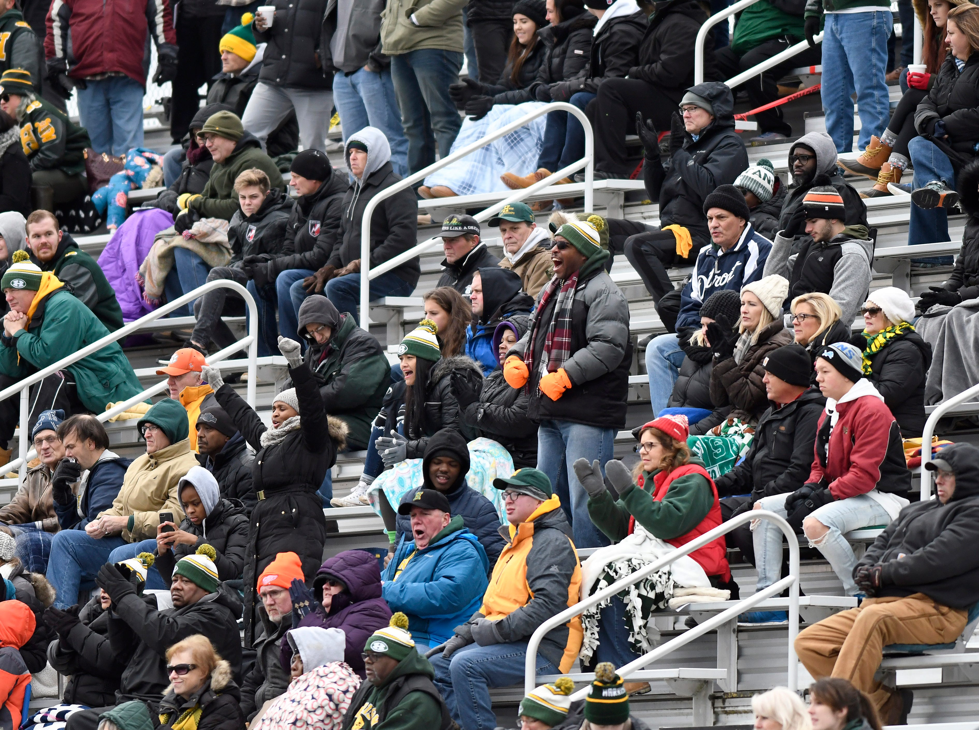 Farmington Hills Harrison fans are bundled up for the cold weather as they cheer on their team against Chelsea in the first quarter.