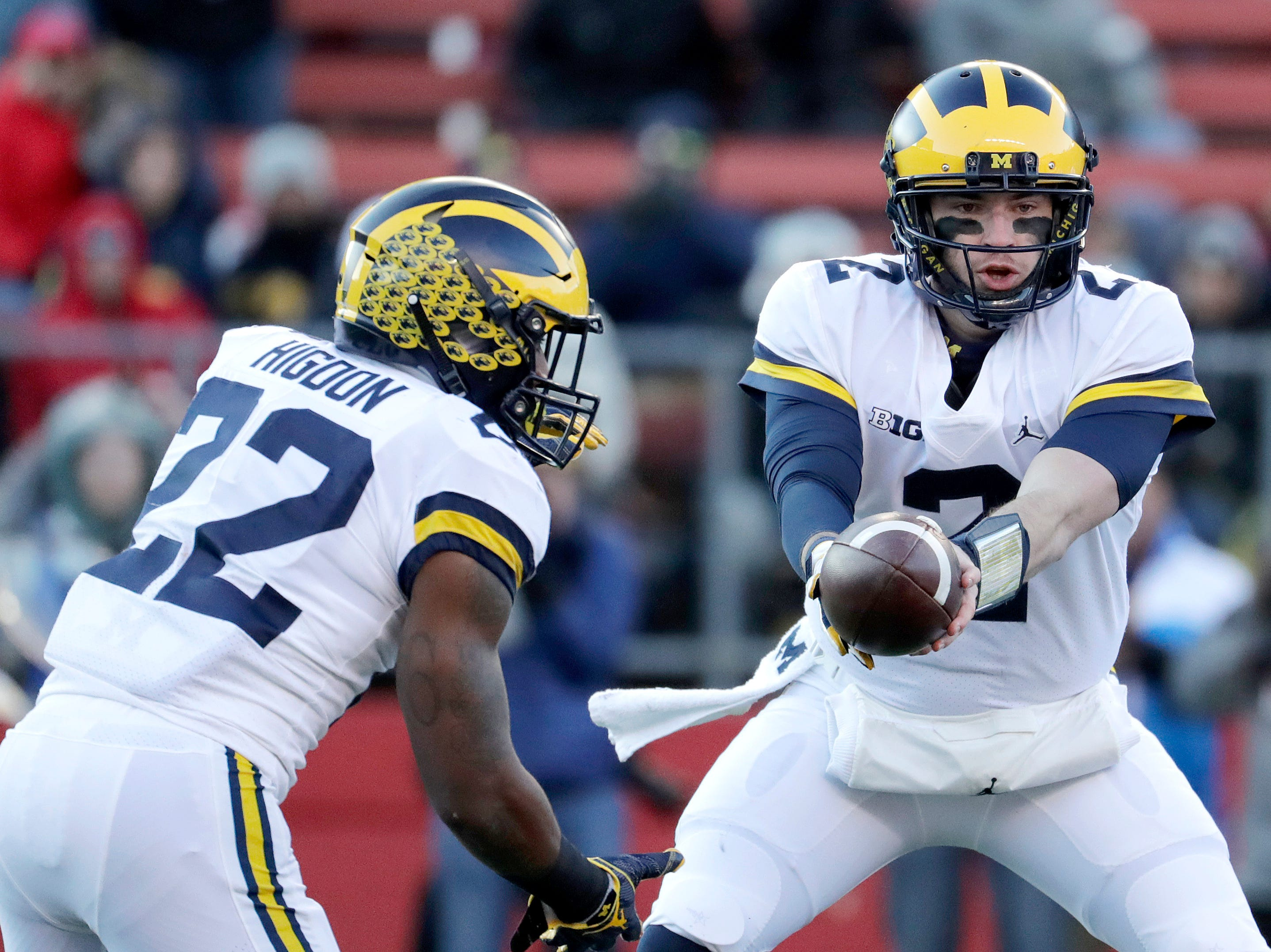 Michigan quarterback Shea Patterson hands off to running back Karan Higdon .