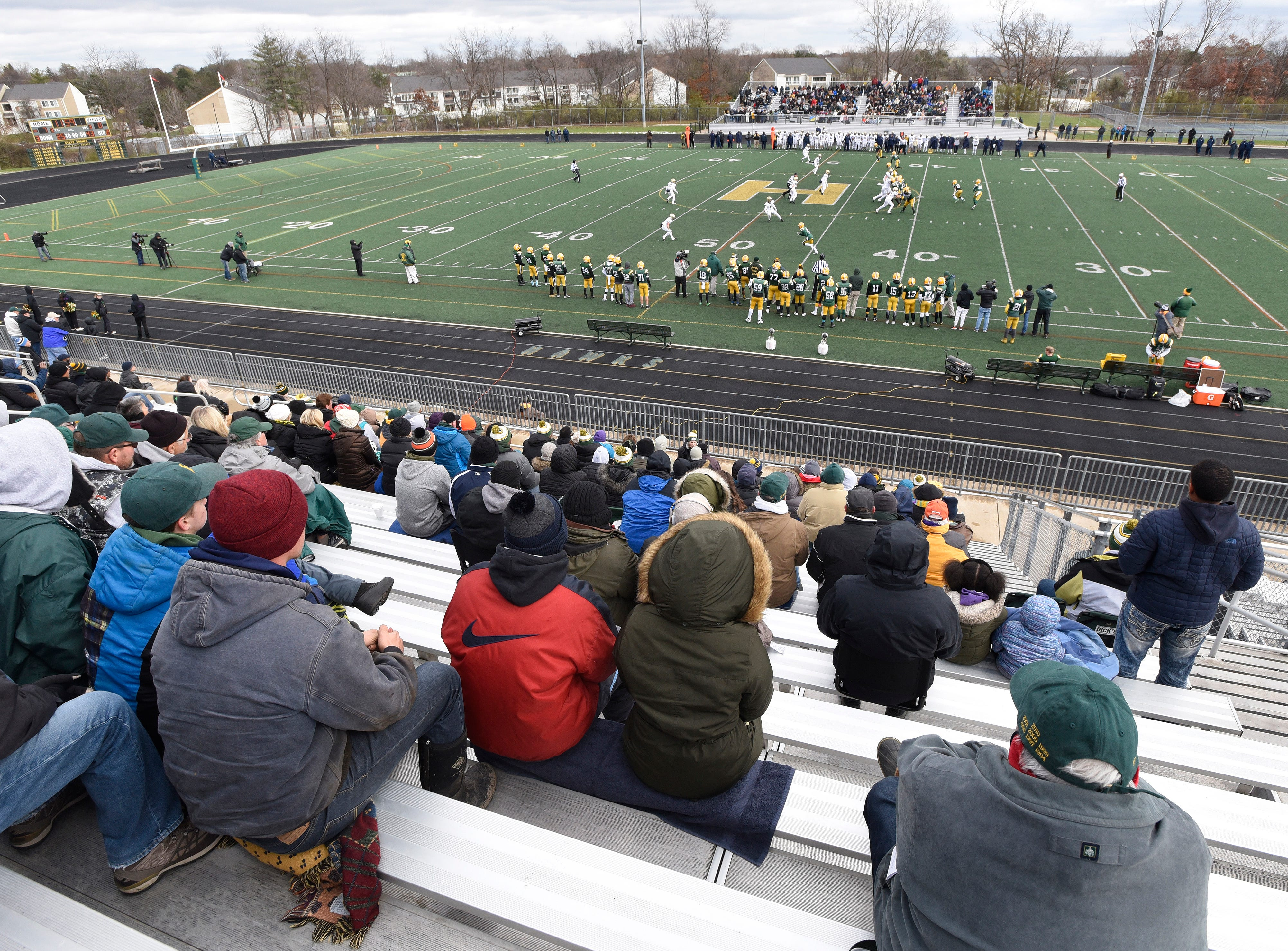 A small group of Farmington Hills Harrison fans brave the cold weather as they watch their team play against Chelsea in the second quarter.