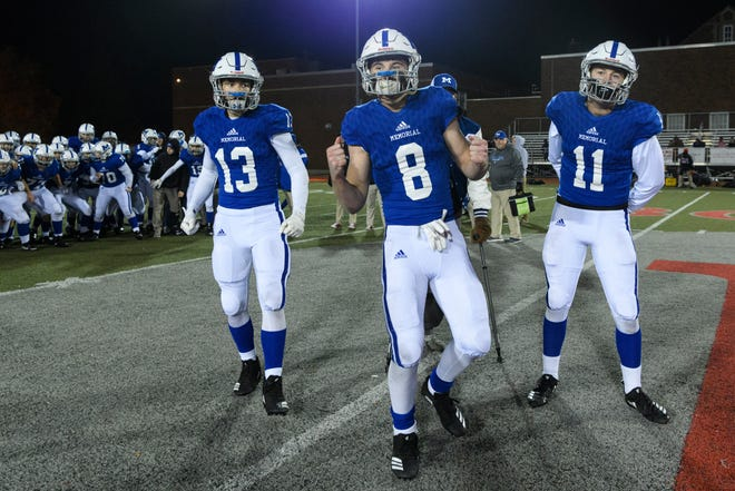 Memorial's Evan Janiga (13), Branson Combs (8) and Michael Lindauer (11) prepare to receive the regional championship plaque on Enlow Field in Evansville, Ind., Friday, Nov. 9, 2018. The Tigers defeated the Braves, 56-14, to advance to next weekend's semistate match against Bishop Chatard.