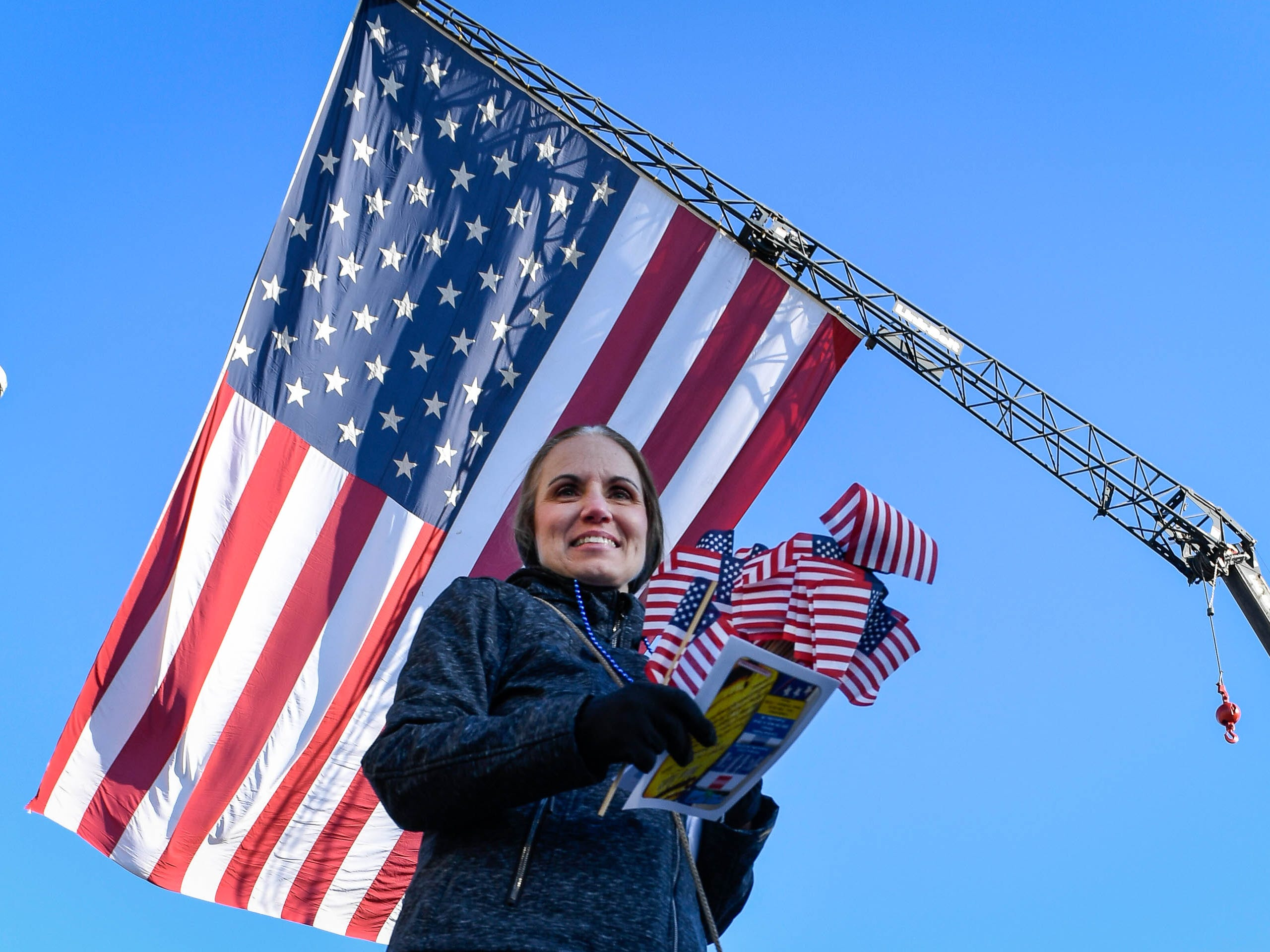 Aprile Sandefur hands out flags at the annual Four Freedoms Veterans Parade on Evansville's West Franklin Street Saturday, November 10, 2018.