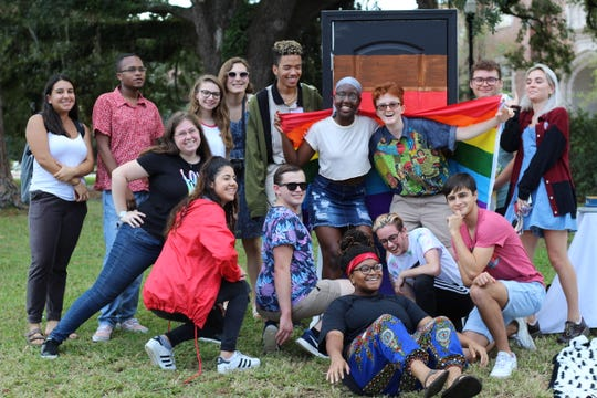 Pride Student Union members gather for a photo next to their display on Landis Green, which celebrated National Coming Out Day.