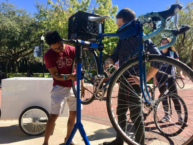 Julio Mata, reCycle Bike Coordinator, repairs the bike of former reCycle Bike Coordinator Alberto De Los Rios in front of the Integration Statue.