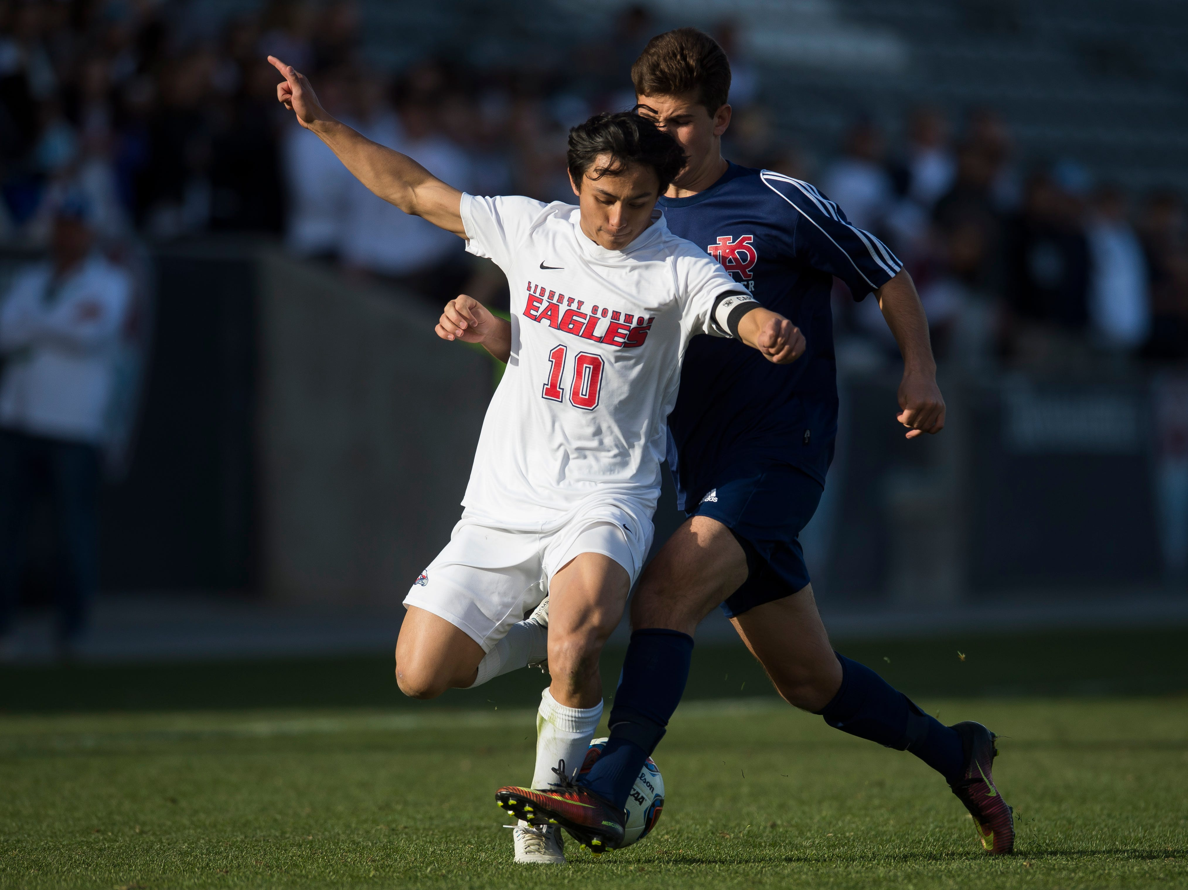 Liberty Common senior midfielder Michael Yeh (10) gets tripped up by Kent Denver sophomore Davis Evans (23) during the state 3A championship game on Saturday, Nov. 10, 2018, at Dick's Sporting Goods park in Commerce City, Colo.