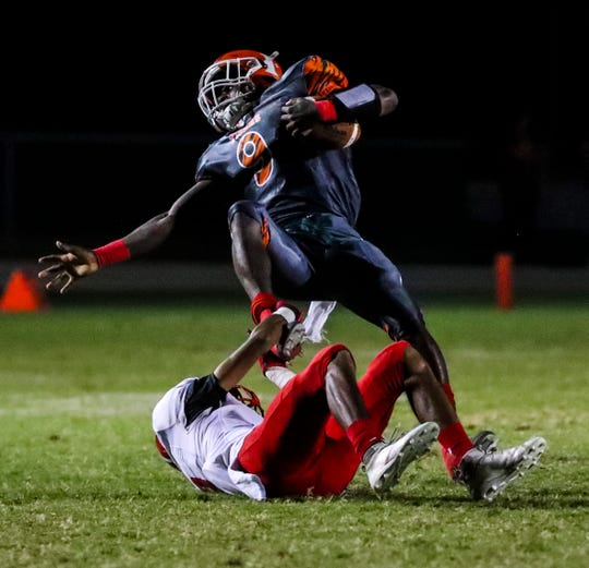 Dunbar's Seneca Milledge is tripped up by Immokalee's Jodeci Chappa. Action from the Immokalee at Dunbar high school football regional quarterfinal game.