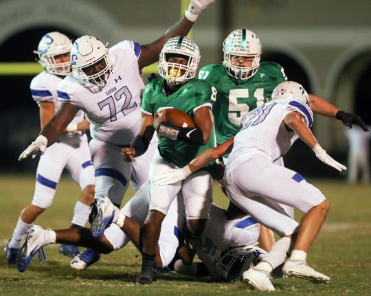 Fort Myers High School's Willie Neal breaks free from Barron Collier defenders on Friday at Sam Sirianni Field in Fort Myers. Fort Myers beat Barron 42-14.