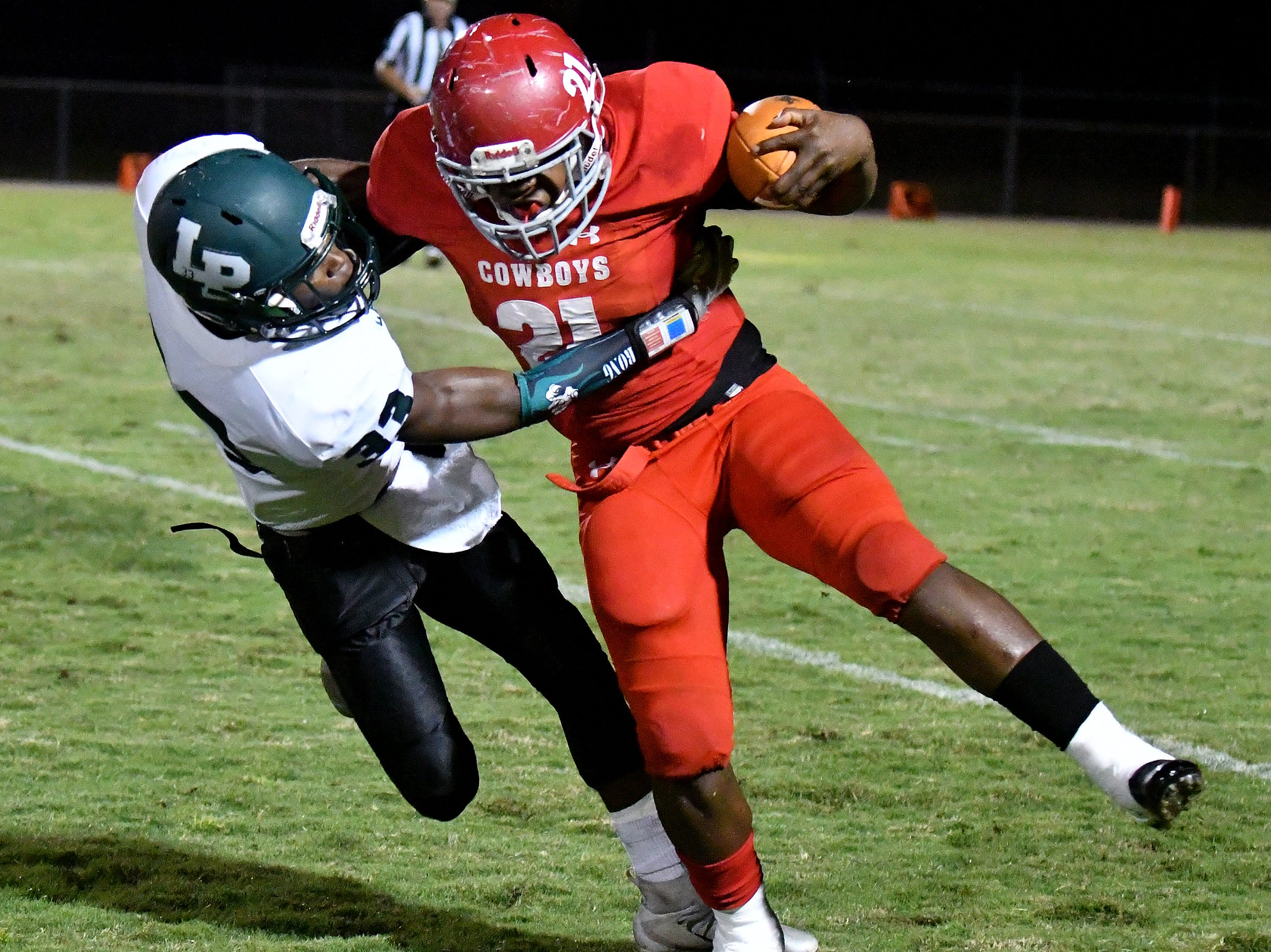 LaBelle High School's Maynard Blackmon runs the ball while fighting off a Lake Placid High School defender during their game on Friday, Nov. 9.