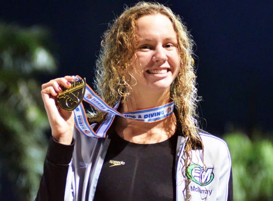 Fort Myers sophomore Olivia McMurray holds up her state championship medal won in the girls 200-yard freestyle at the FHSAA Class 3A state finals on Friday at Sailfish Splashpark Aquatic Center in Stuart. She posted an automatic All-American time.