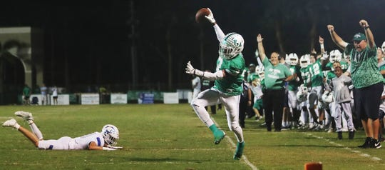 Fort Myers High School's John Coleus breaks free from Barron Collier defenders on Friday at Sam Sirianni Field in Fort Myers. Fort Myers beat Barron 42-14.