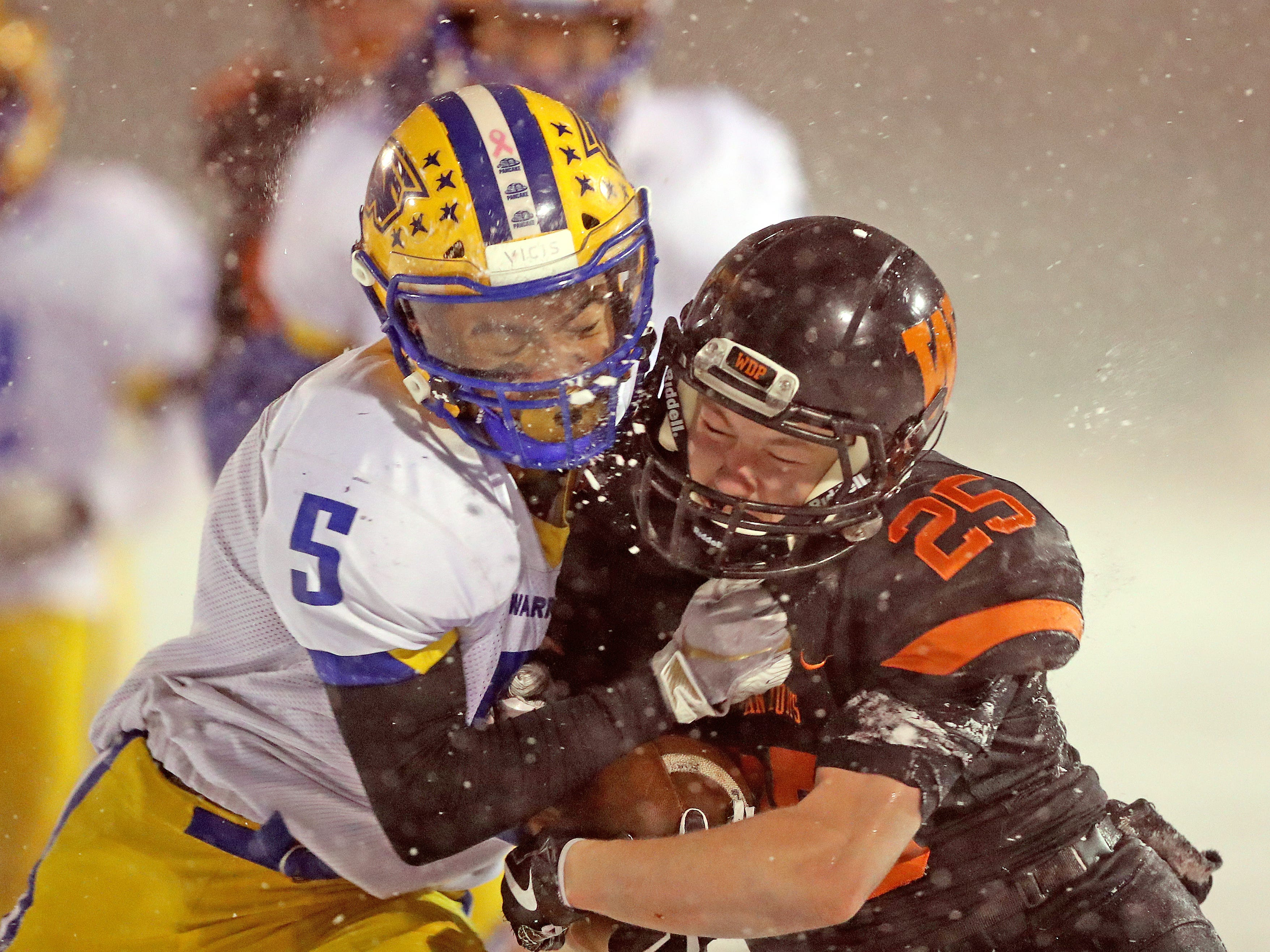 West De Pere's Kaden Kosobucki gets hit hard on a long run by Rice Lake's DeAirus Clerveaux in the Division 3 Level 4 WIAA playoffs Friday, November 9, 2018 at DC Everest in Weston, Wis.