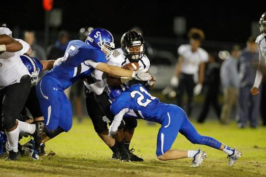 Gaffney's Ray Johnson (30) is sandwiched by Woodmont's Cooper Nicholson (5) and Woodmont's Cal Drummond (21) Friday, November 9, 2018 during the first round of the Class AAAAA football playoffs at Whitt Memorial Field.