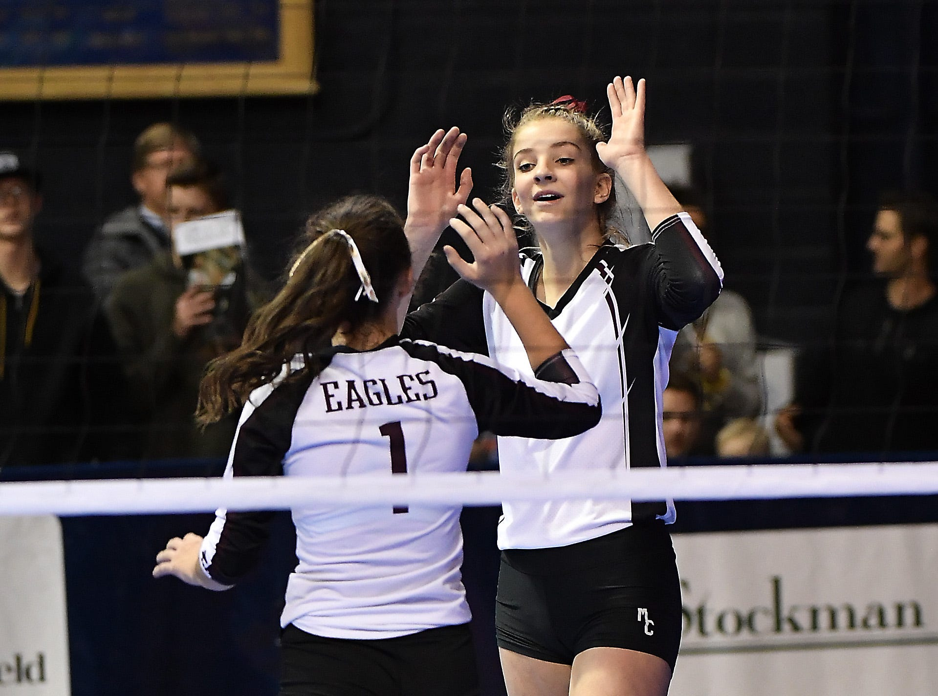 Kierstin Van Kirk and Taylor Devries (1) of Manhattan Christian celebrate during a match with Tri-Cities at the All-Class State Volleyball Tournament at the Brick Breeden Fieldhouse in Bozeman Friday.