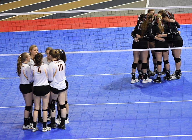 The Belt Huskies and Simms Tigers huddle up before the Class C undefeated semifinal match at the All-Class State Volleyball Tournament at the Brick Breeden Fieldhouse in Bozeman Friday.
