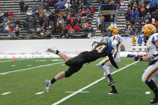 Great Falls Central's Cayle Schraner dives to make a tackle on Fairview's Jesse Selting during the Mustangs' Eight-Man playoff semifinal victory last season.