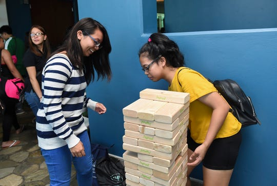 Ericka Gatus, right, and Nichole Hernandez play a game of Tumbling Towers during the Bank of Guam's second annual Life Teen Expo at Skinner Plaza in Hagåtña, Nov. 10, 2018.