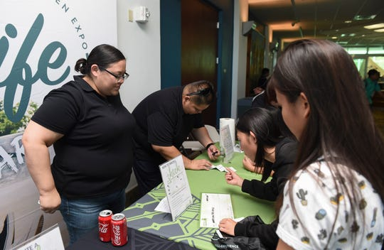Teens learn how to write checks from Bank of Guam representatives during the Bank of Guam's second annual Life Teen Expo at Skinner Plaza in Hagåtña, Nov. 10, 2018.