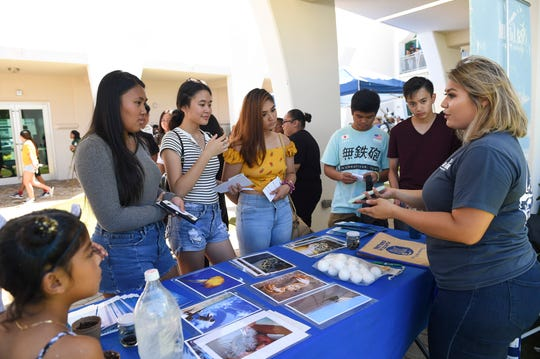 Teens visit a University of Guam Sea Grant Program booth during the Bank of Guam's second annual Life Teen Expo in Hagåtña, Nov. 10, 2018.