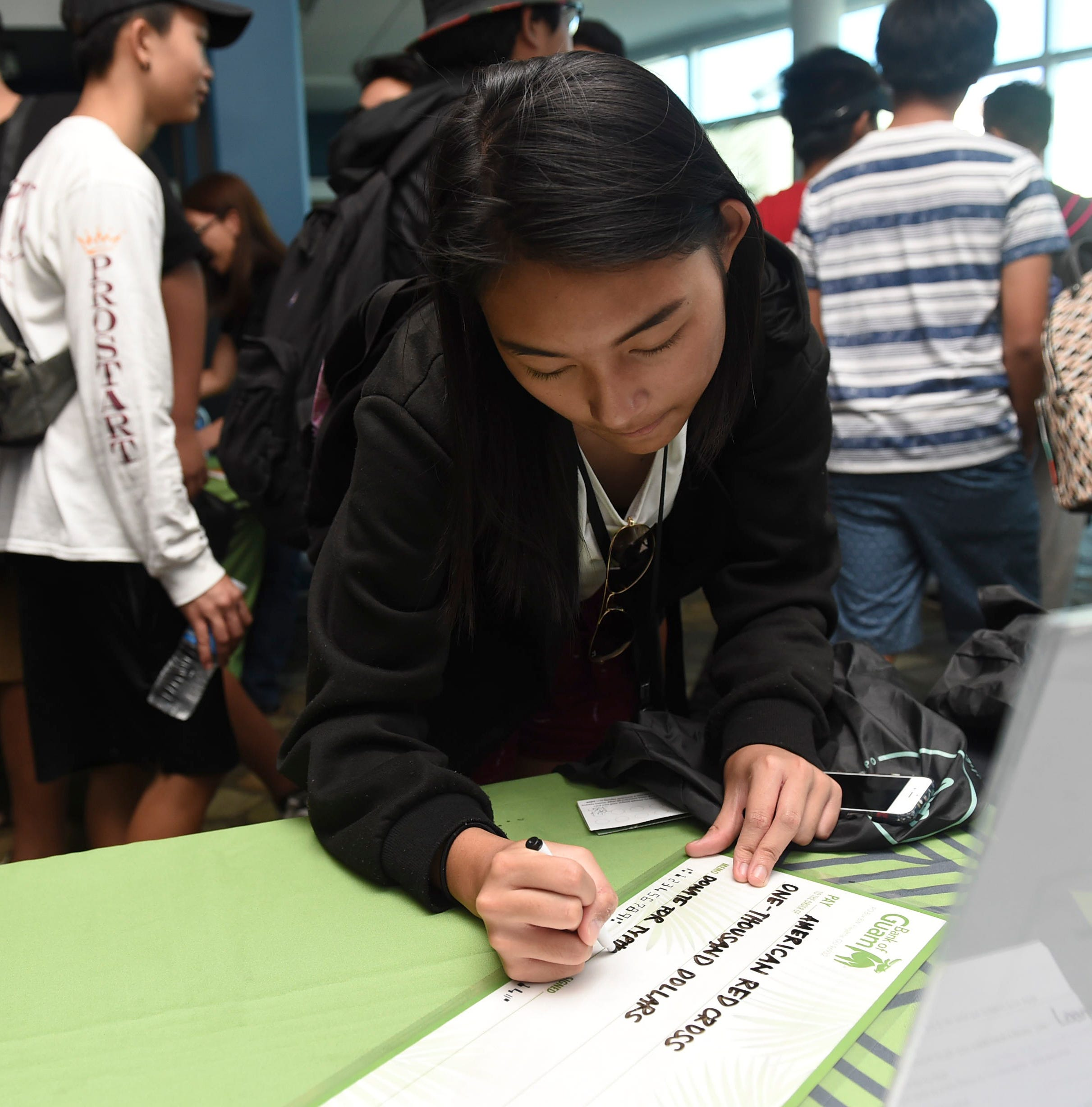 A teen learns how to write a check during the Bank of Guam's second annual Life Teen Expo at Skinner Plaza in Hagåtña in this Nov. 10, 2018, file photo. The 2021 Youth Employment Internship Program by Guam Department of Education's and the Department of Youth Affairs will run June 21 to Aug. 13.