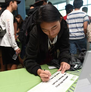 A teen learns how to write a check during the Bank of Guam's second annual Life Teen Expo at Skinner Plaza in Hagåtña, Nov. 10, 2018.