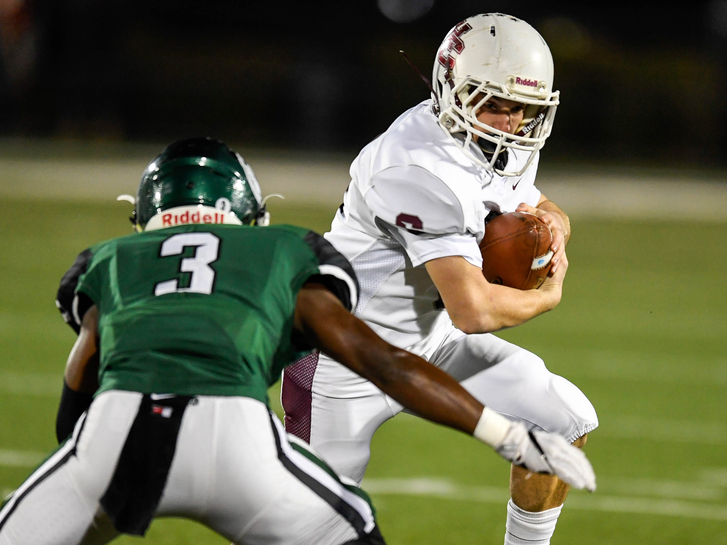 Henderson's Logan Green (6) tries to get past defense from Trinity's David Florence (3) as the Henderson County Colonels play the Trinity Shamrocks in the second round of the Class 6-A football playoffs at Marshall Stadium in Louisville Friday, November 9, 2018.