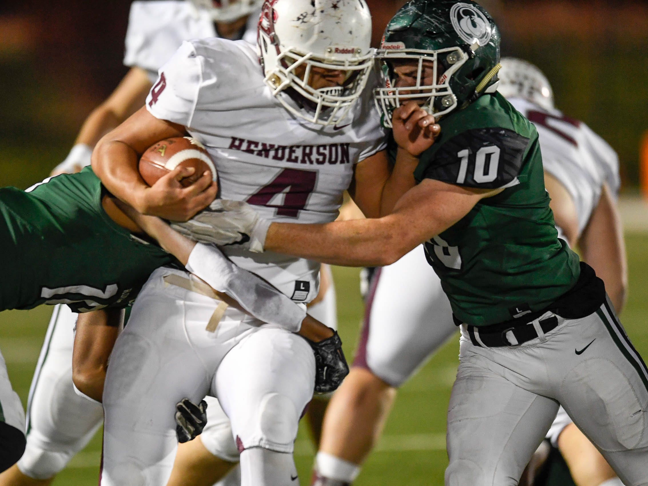 Henderson's Layton Fletcher (4)  runs between defense from Trinity's Blake Ruffin (16) and Charlie Ely (10) as the Henderson County Colonels play the Trinity Shamrocks in the second round of the Class 6-A football playoffs at Marshall Stadium in Louisville Friday, November 9, 2018.