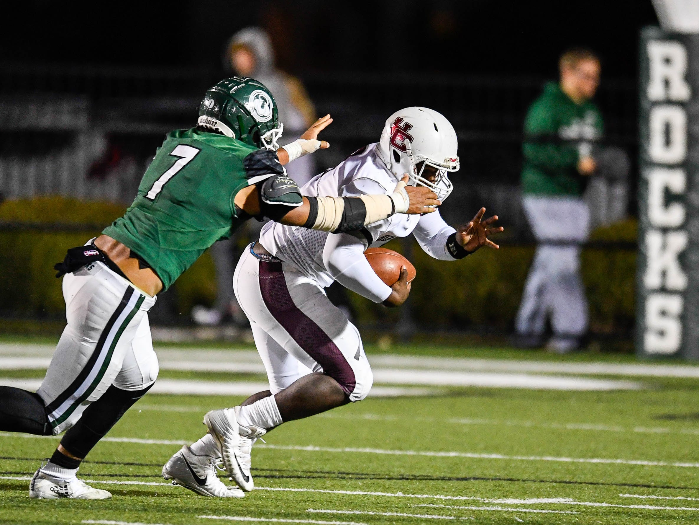 Henderson quarterback Skip Patterson (1) chased by Trinity's Stephen Herron (7) as the Henderson County Colonels play the Trinity Shamrocks in the second round of the Class 6-A football playoffs at Marshall Stadium in Louisville Friday, November 9, 2018.