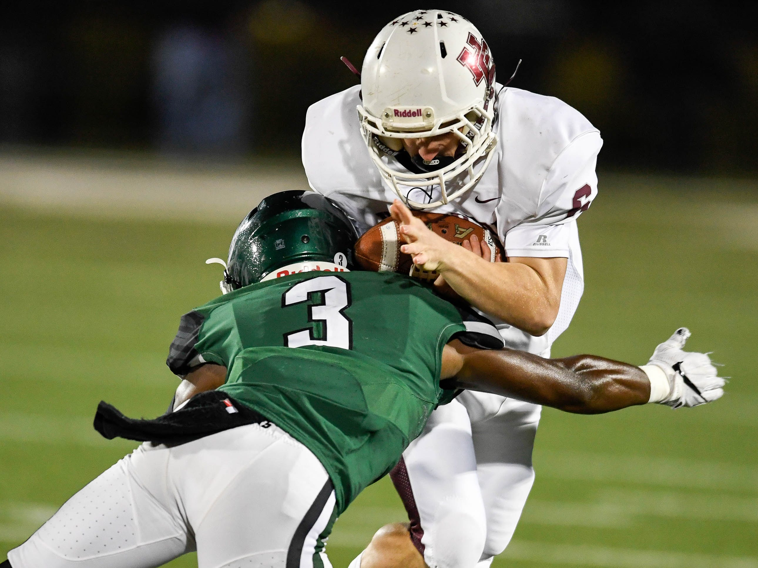 Henderson's Logan Green (6) is tackled by Trinity's David Florence (3) as the Henderson County Colonels play the Trinity Shamrocks in the second round of the Class 6-A football playoffs at Marshall Stadium in Louisville Friday, November 9, 2018.