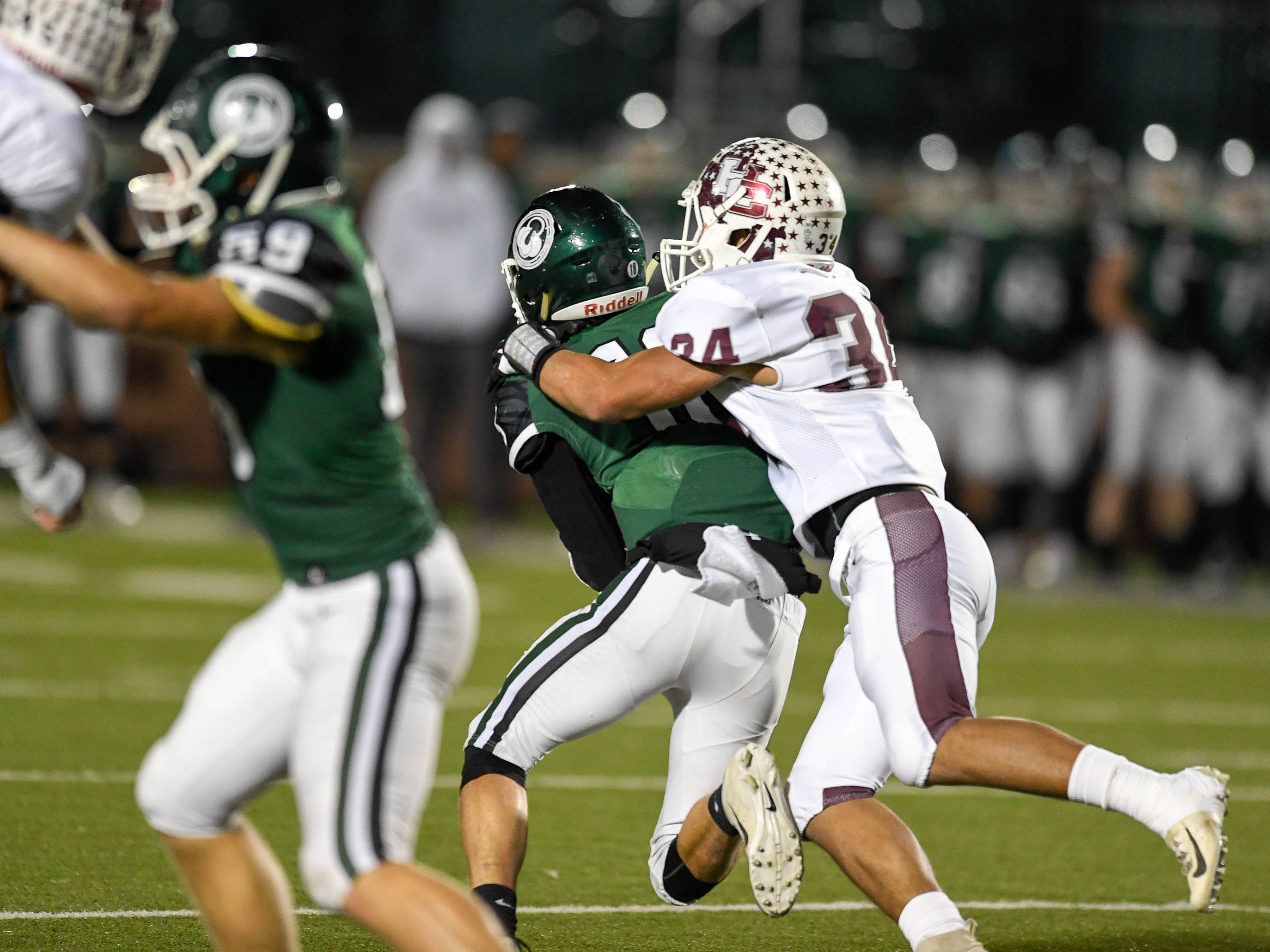 Henderson's Isaiah Fallen (34)  drags down Trinity quarterbqack Seth Jutz (18) for a sack as the Henderson County Colonels play the Trinity Shamrocks in the second round of the Class 6-A football playoffs at Marshall Stadium in Louisville Friday, November 9, 2018.