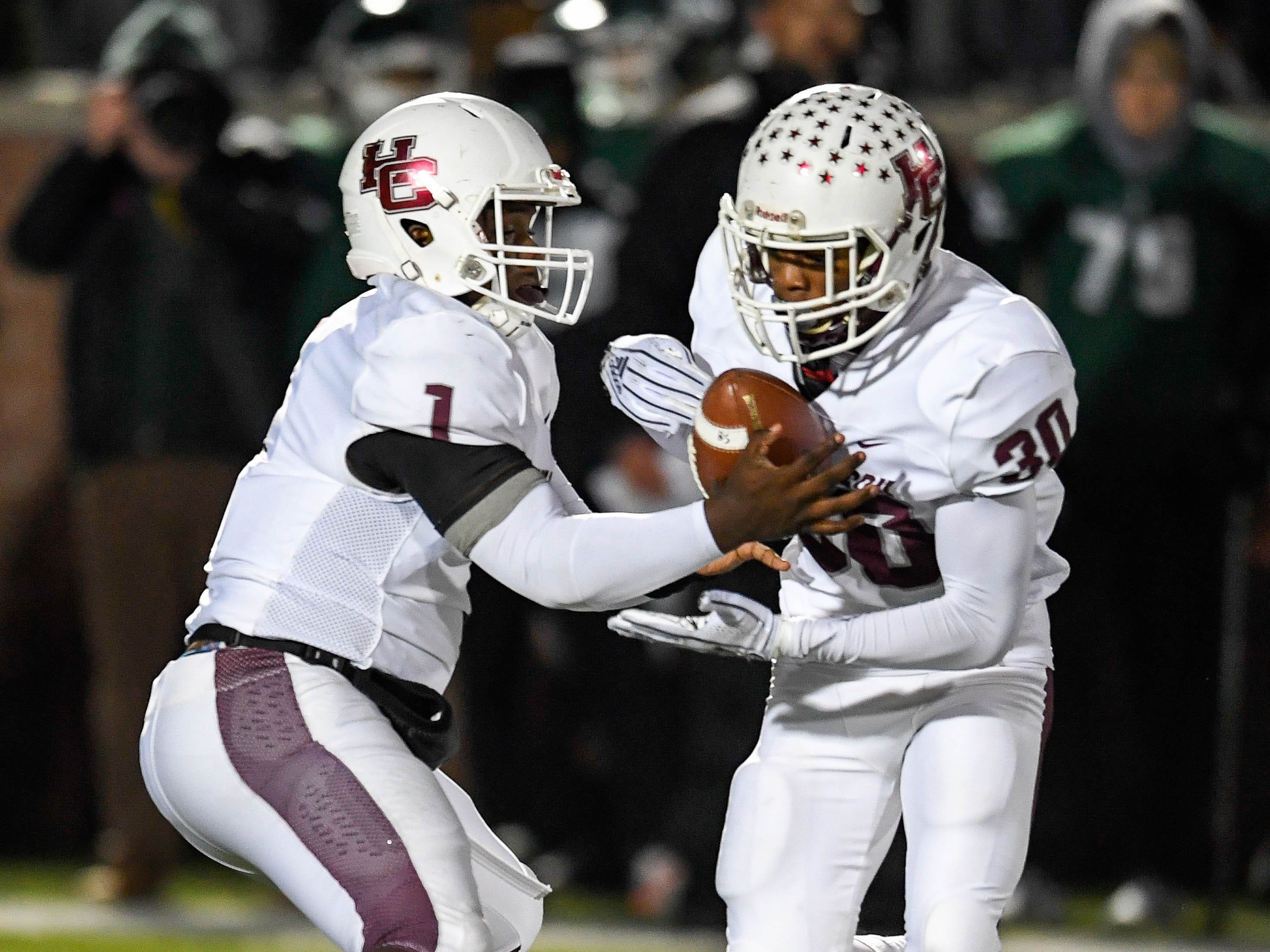 Henderson quarterback Skip Patterson (1) hands off to Henderson's Isaiah Easley (30) as the Henderson County Colonels play the Trinity Shamrocks in the second round of the Class 6-A football playoffs at Marshall Stadium in Louisville Friday, November 9, 2018.