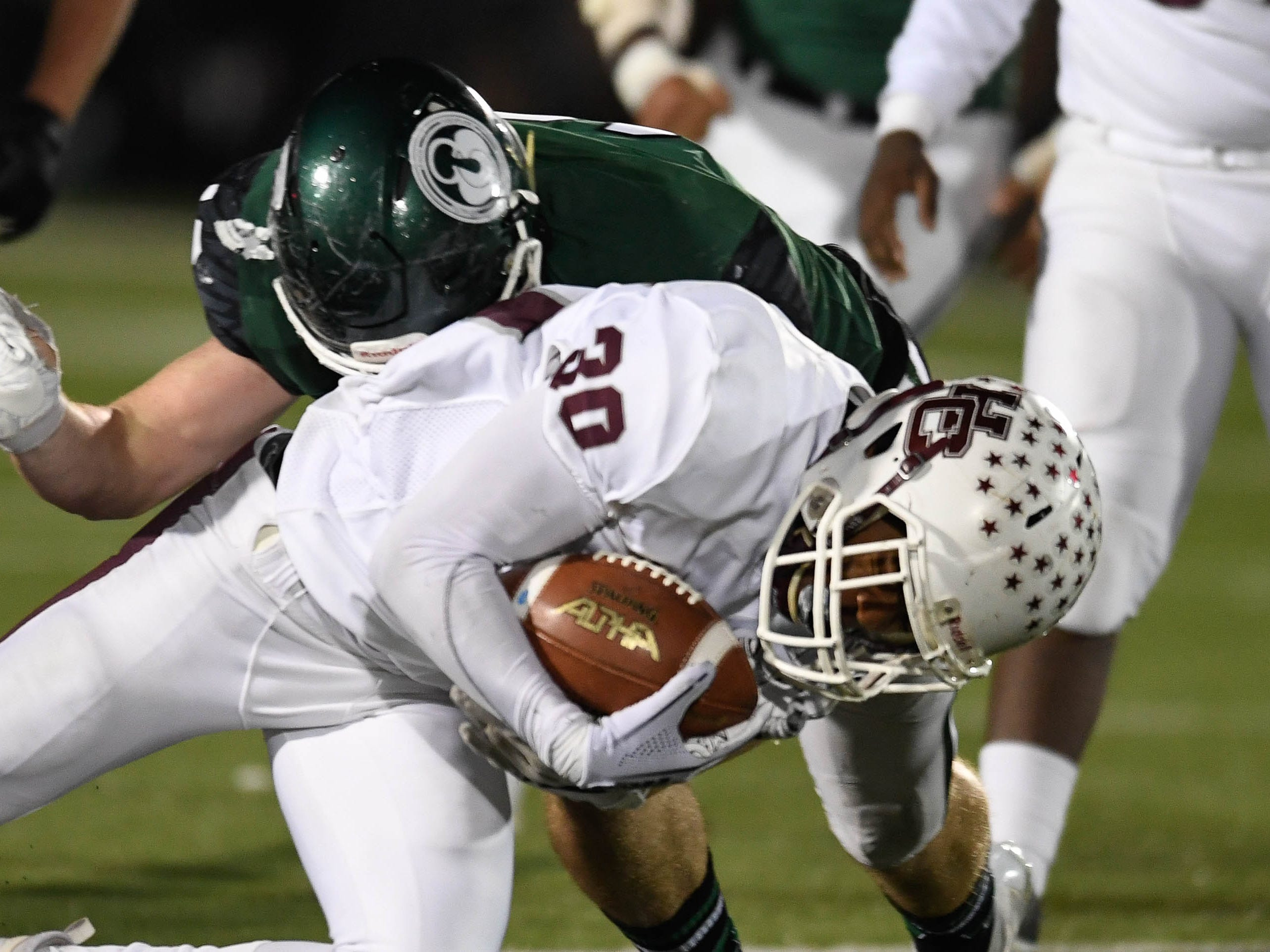 Henderson's Isaiah Easley (30) digs for extra yards as the Henderson County Colonels play the Trinity Shamrocks in the second round of the Class 6-A football playoffs at Marshall Stadium in Louisville Friday, November 9, 2018.