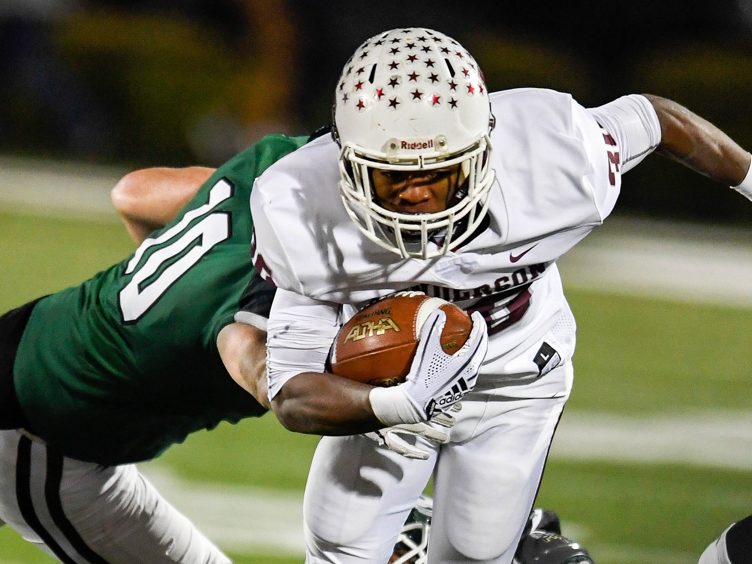 Henderson's Isaiah Easley (30) tries to run past defense from Trinity's Charlie Ely (10) as the Henderson County Colonels play the Trinity Shamrocks in the second round of the Class 6-A football playoffs at Marshall Stadium in Louisville Friday, November 9, 2018.