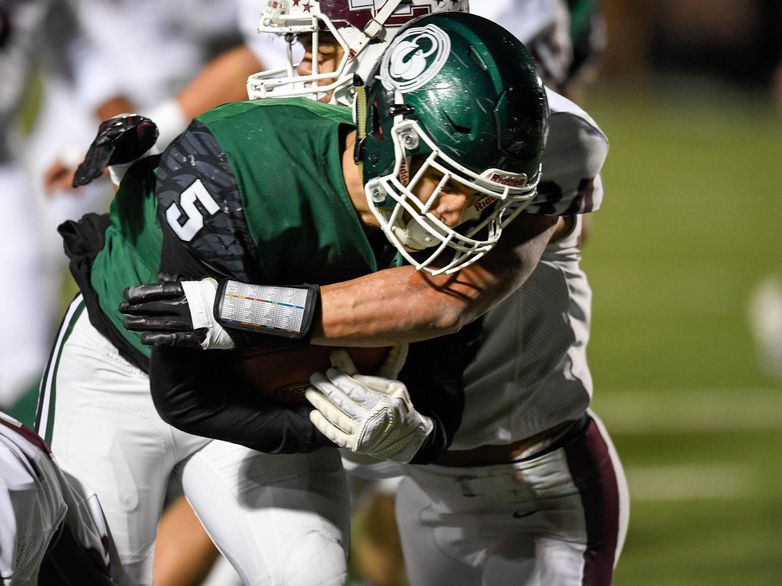 Henderson's Isaiah Fallen (34) wraps up Trinity's Luke McGuire (5) as the Henderson County Colonels play the Trinity Shamrocks in the second round of the Class 6-A football playoffs at Marshall Stadium in Louisville Friday, November 9, 2018.
