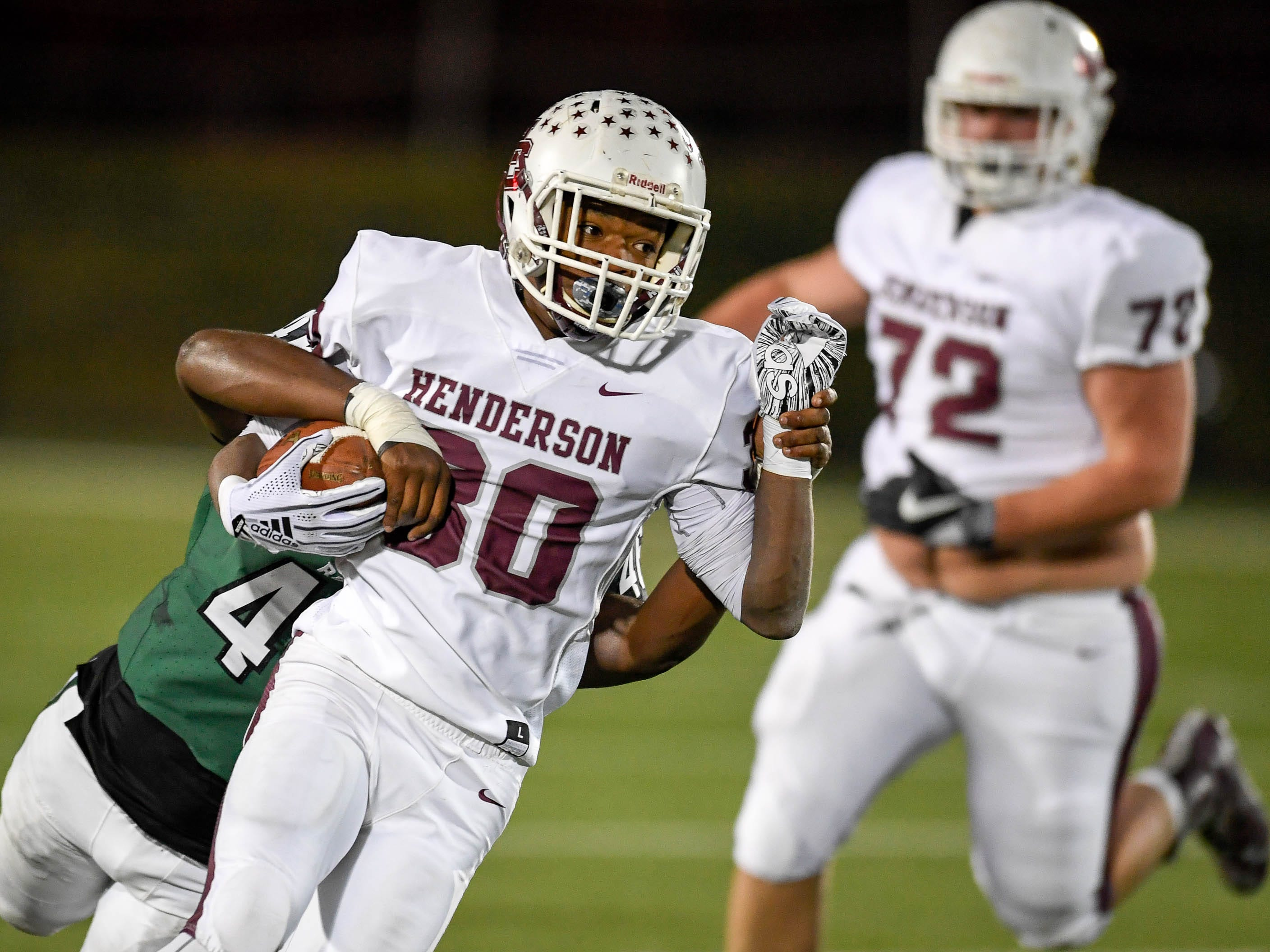 Henderson's Isaiah Easley (30) looks for running room with Trinity's Tyler Roberson (46) hanging on as the Henderson County Colonels play the Trinity Shamrocks in the second round of the Class 6-A football playoffs at Marshall Stadium in Louisville Friday, November 9, 2018.