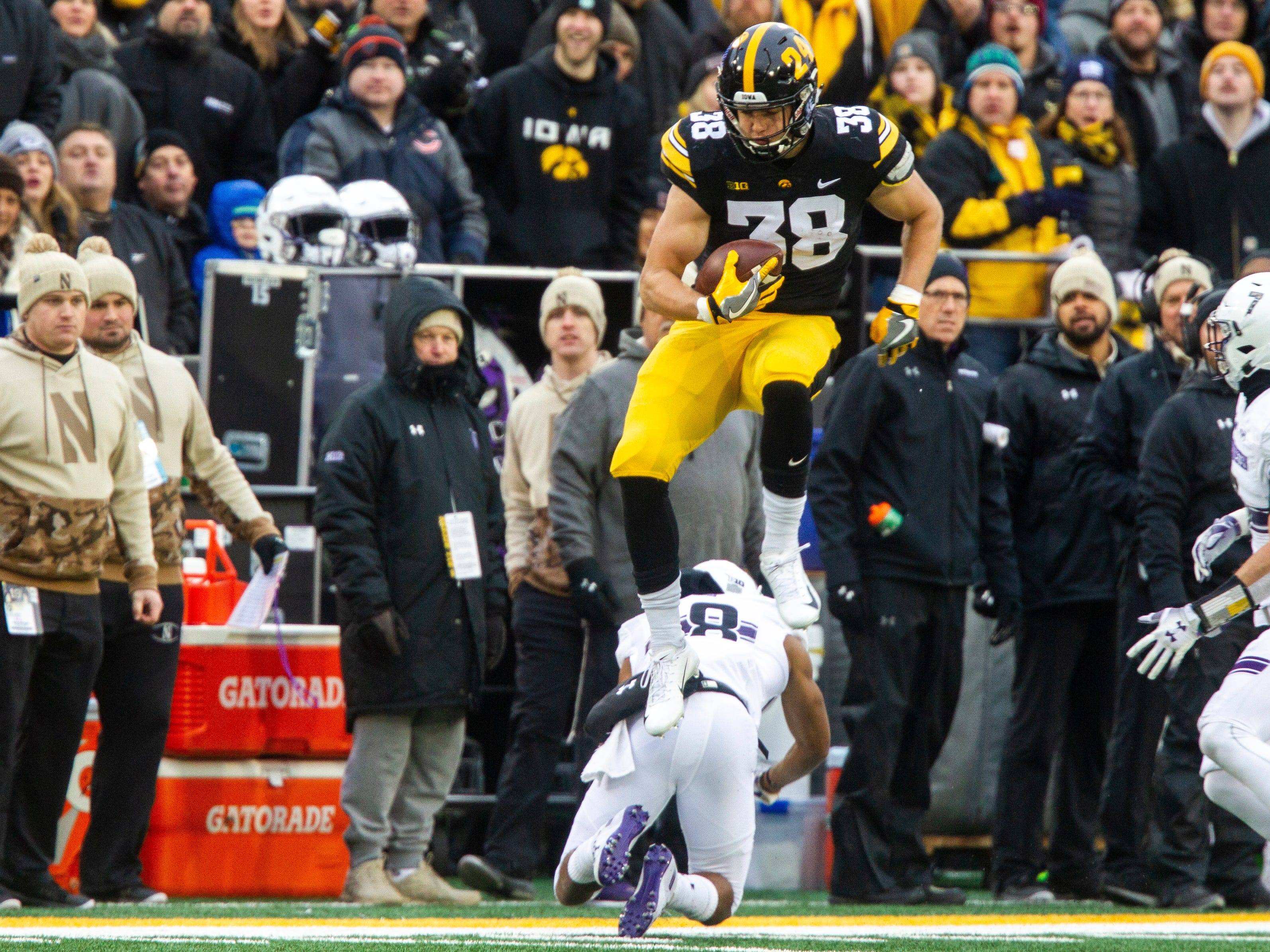 Iowa tight end T.J. Hockenson (38) jumps over a defender during a Big Ten Conference football game on Saturday, Nov. 10, 2018, at Kinnick Stadium in Iowa City.