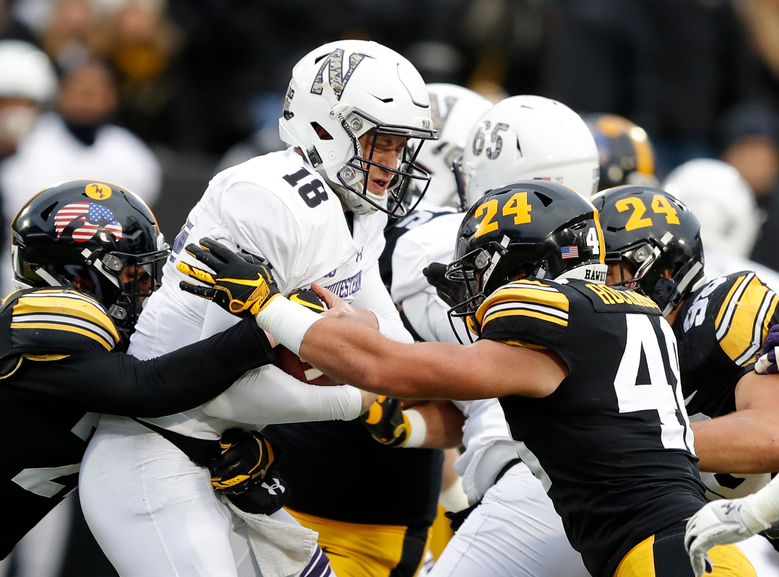 Northwestern quarterback Clayton Thorson (18) is sacked by Iowa's Amani Hooker, left, and Jack Hockaday, right, during the first half of an NCAA college football game, Saturday, Nov. 10, 2018, in Iowa City, Iowa.