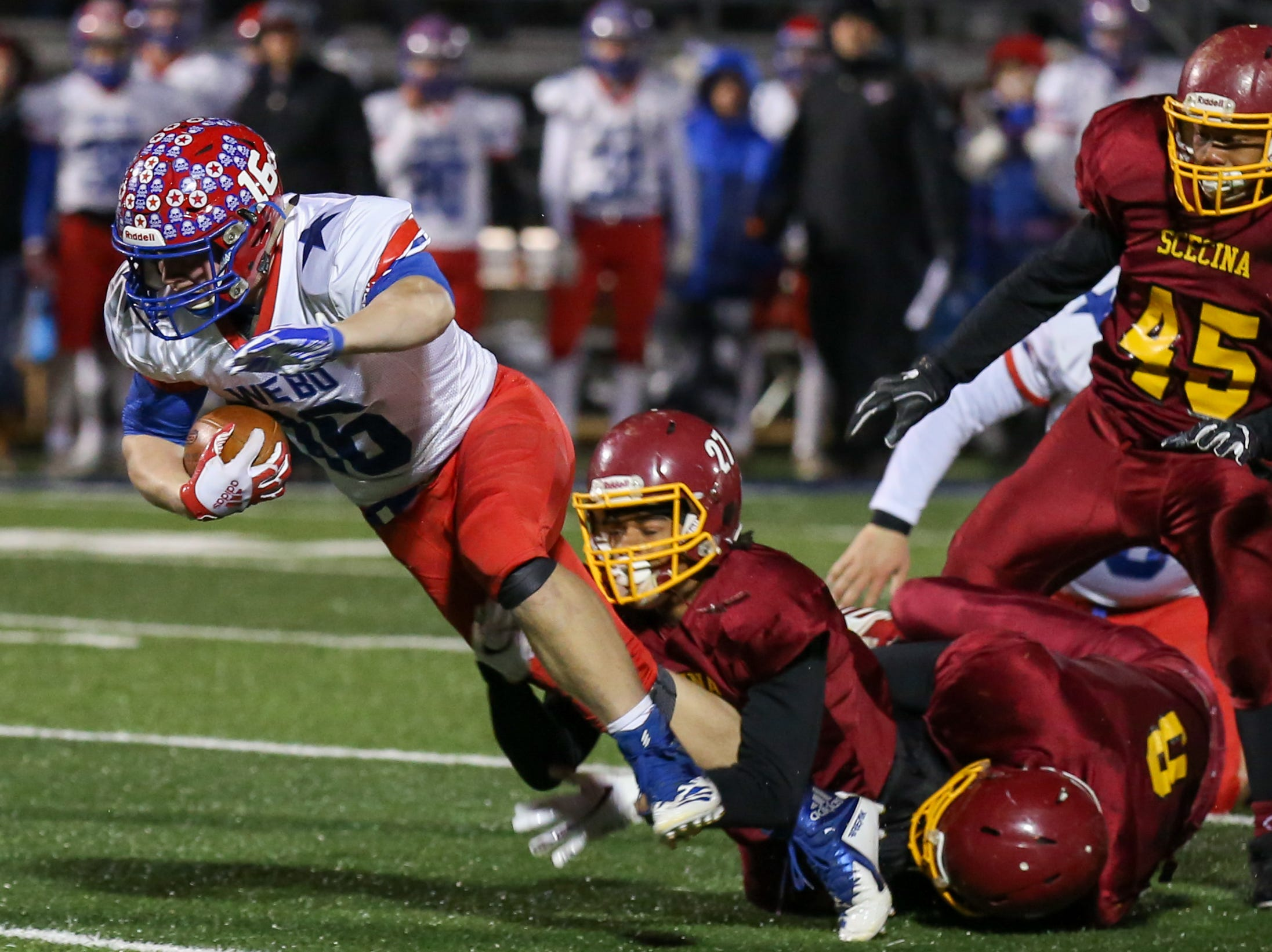 Western Boone's Brett Wethington (16) breaks some tackles for a few extra yards during the first half of Indianapolis Scecina vs Western Boone High School varsity football in the Class 2A Regional Championship held at Roncalli High School, Friday, November 9, 2018.