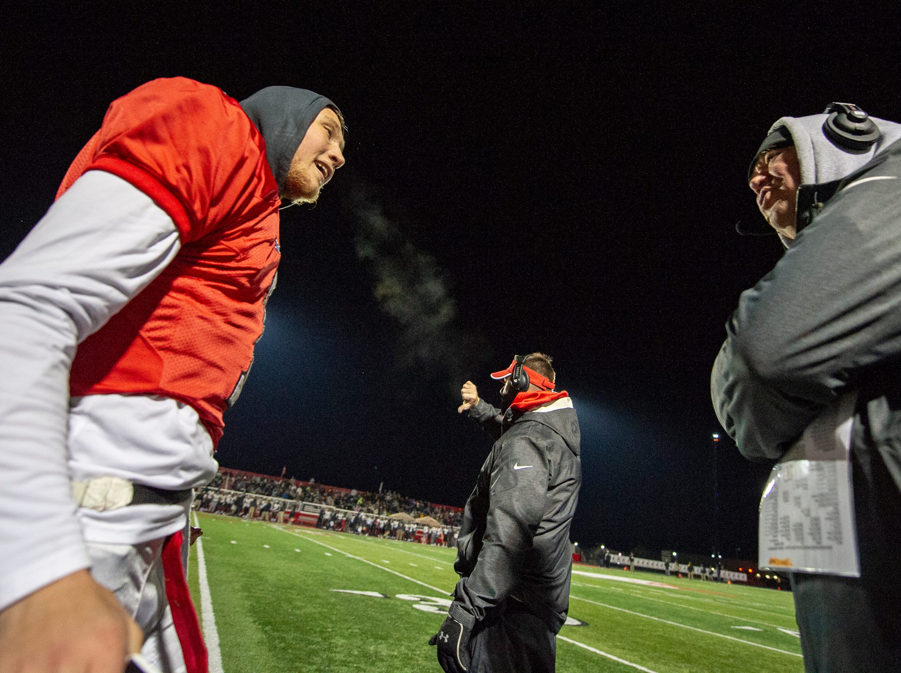 Center Grove High School senior Jack Moore (1) is greeted by his dad and head coach Eric Moore at the sideline during the first half of action. Center Grove High School hosted Avon High School in an IHSAA Class 6A Regional Championship varsity football game, Friday, Nov. 9, 2018.
